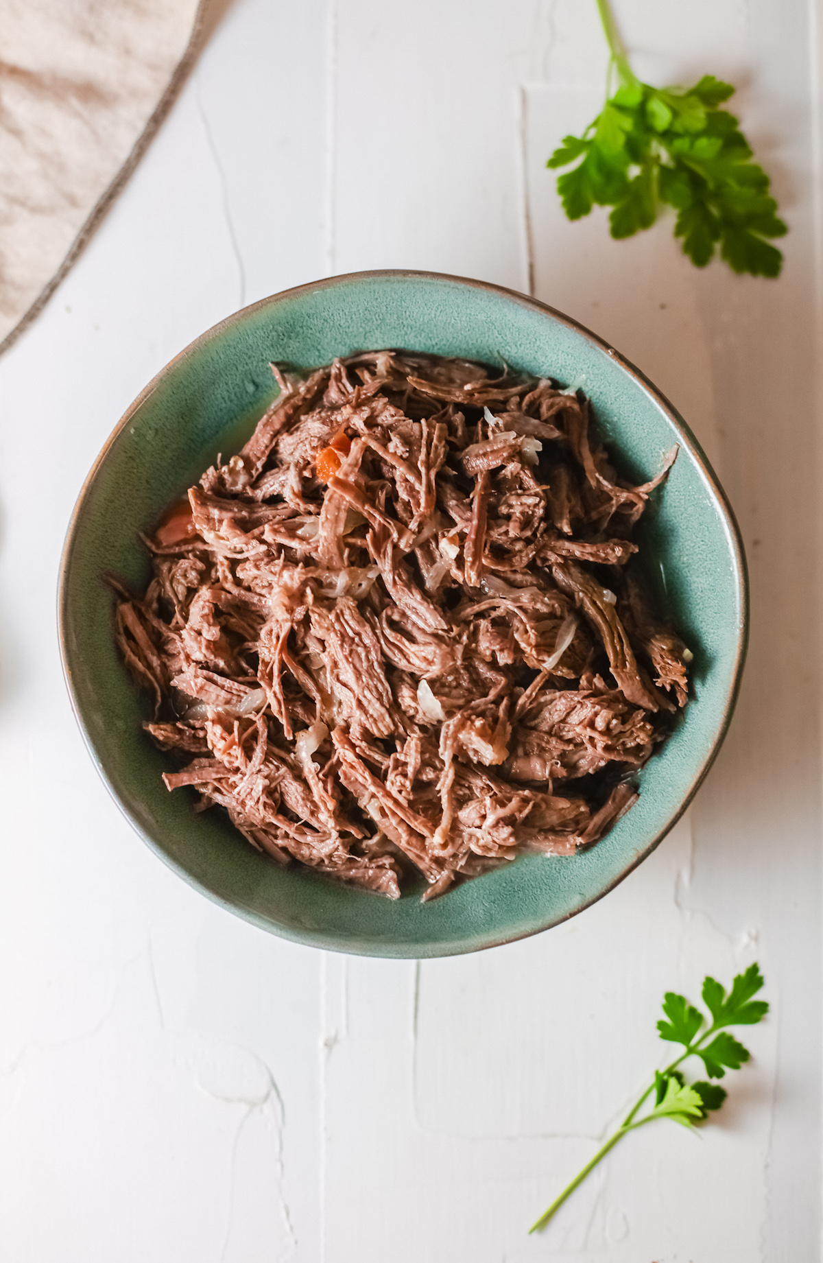 top down view of the finished Instant Pot Barbacoa served in a green ceramic bowl