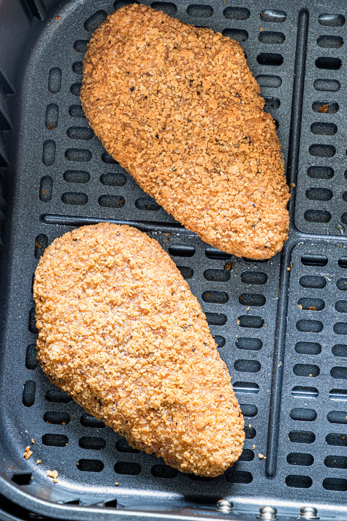 close up view of two pieces of fried chicken inside the air fryer basket