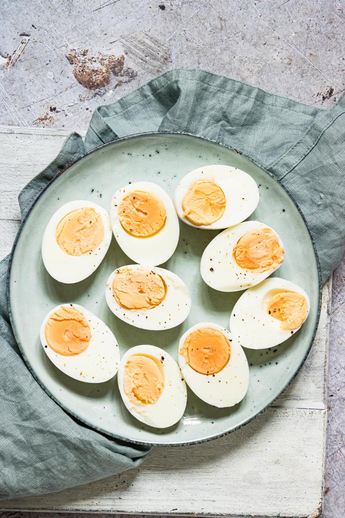 top down view of the completed instant pot hard boiled eggs on a blue plate