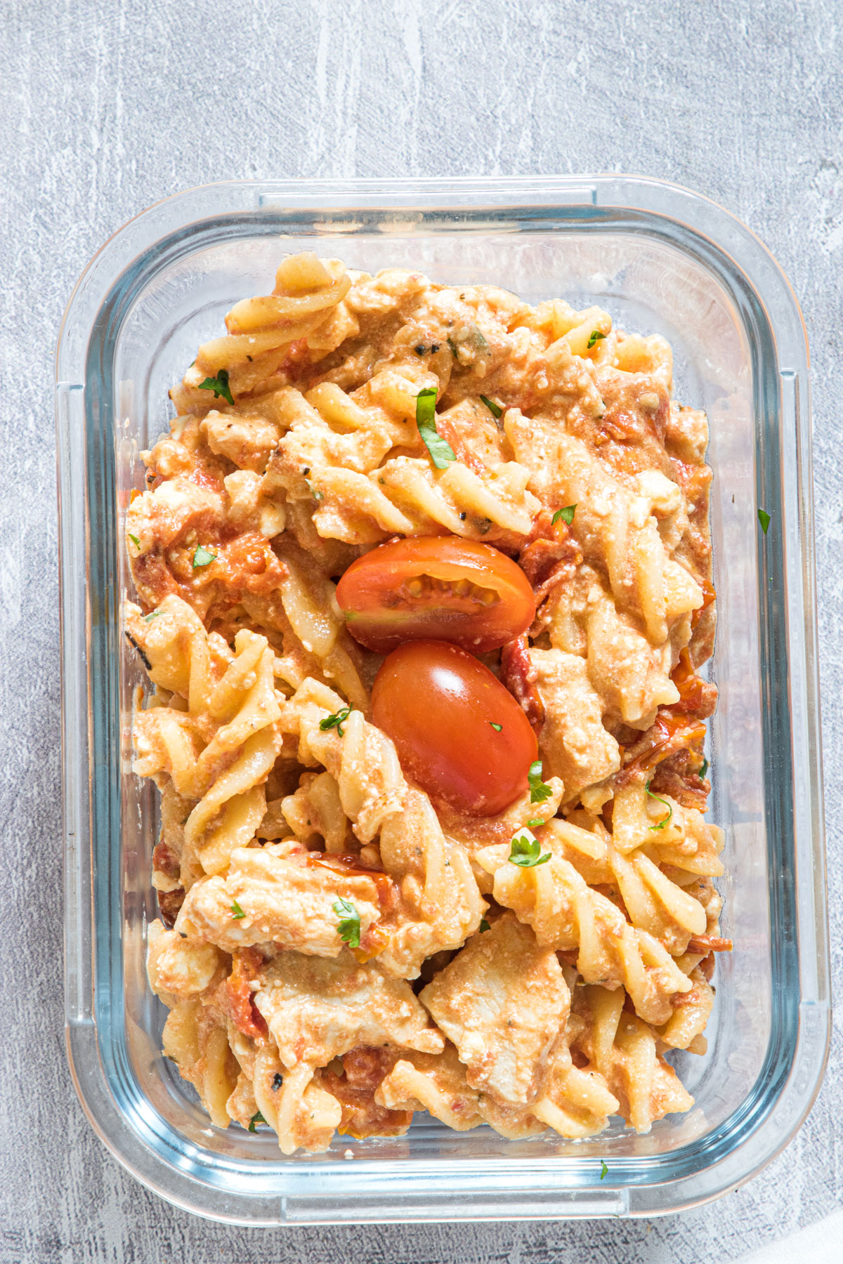 top down view of a serving of buffalo chicken baked feta pasta in a glass food storage container