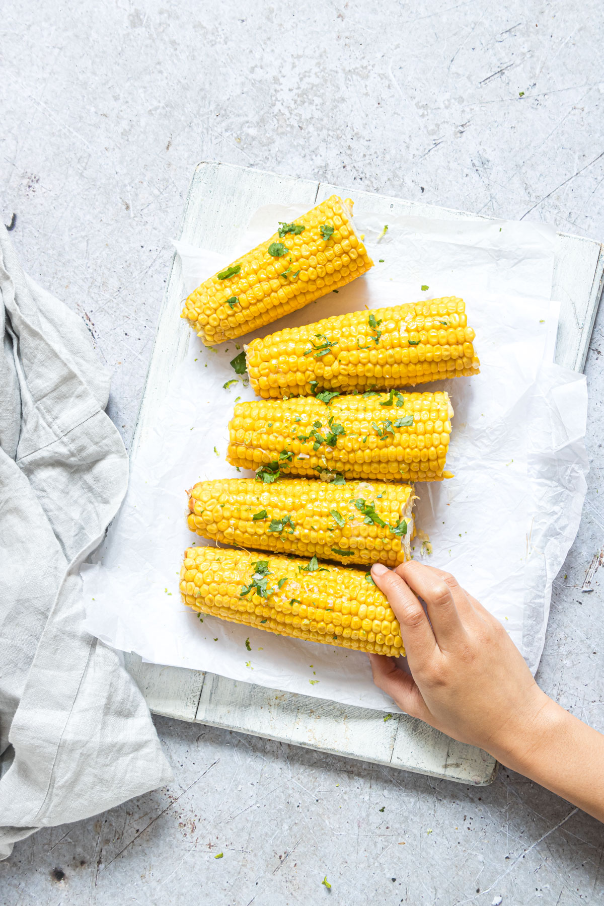 a hand reaching for a piece of instant pot corn on the cob