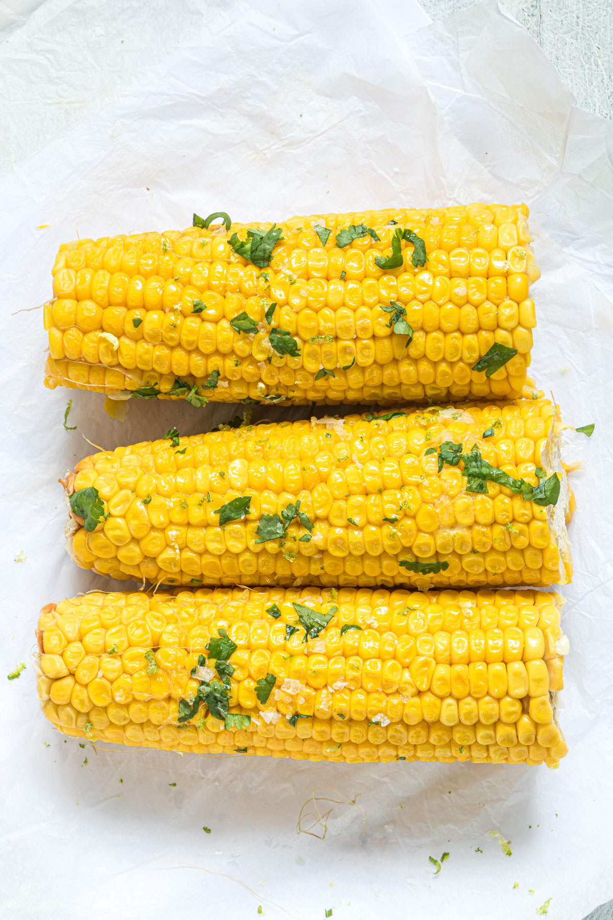 three ears of cooked corn on the cob topped with cilantro