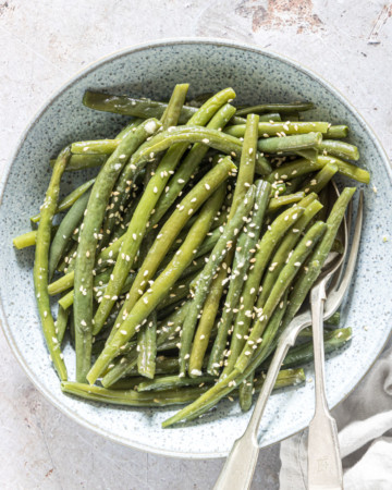 the finished sesame instant pot green beans served in a ceramic bowl with silverware and a cloth napkin