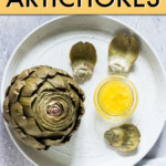 artichokes on a plate with a dish of melted butter