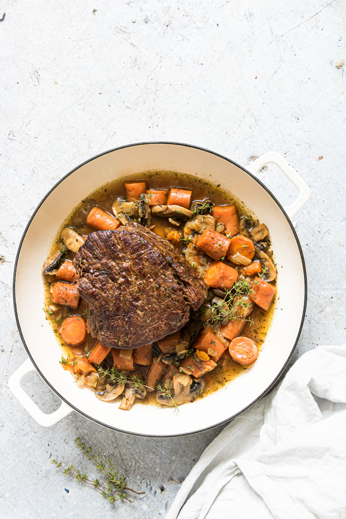A Bowl of Instant Pot Pot Roast On a table with vegetables and garnish