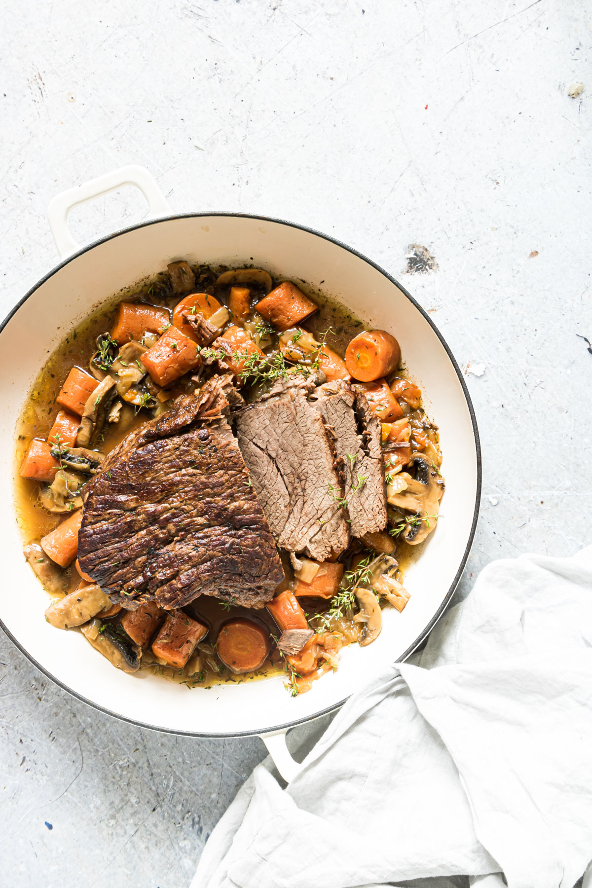 Instant Pot Beef Roast with vegetables on a table with garnish