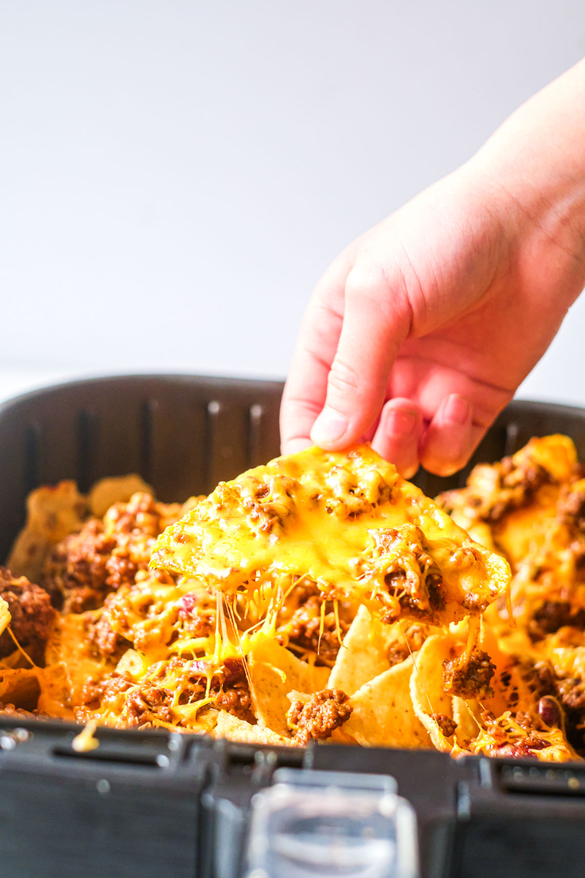 Close up of cheese chili nachos in an air fryer basket