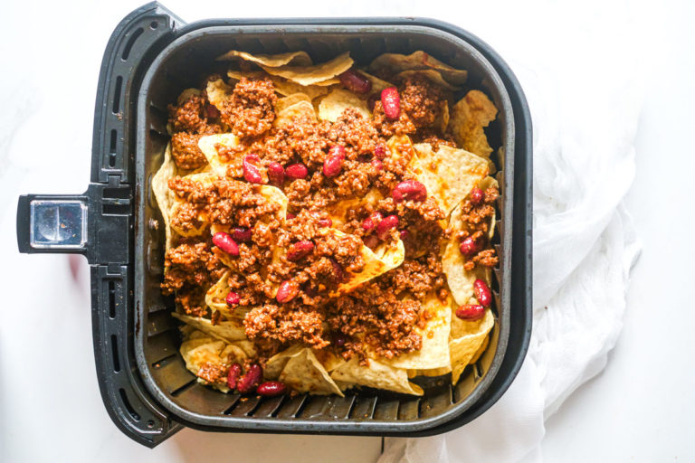 close up with cheese, ground beef chili and tortilla chips  in an air fryer basket