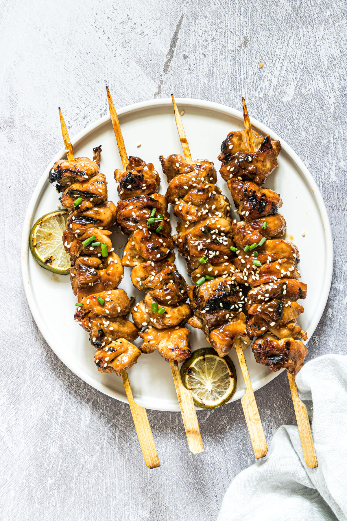 finished Asian grilled chicken kabobs on a white plate and garnished with grilled lime slices