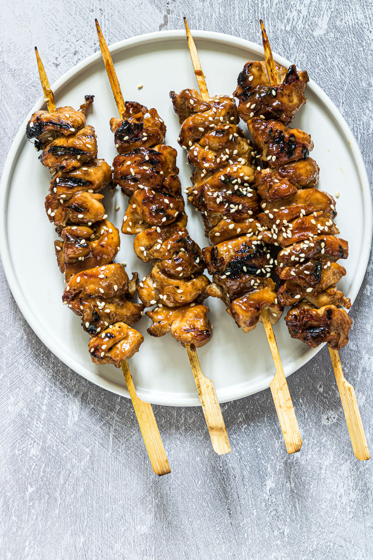 four grilled chicken skewers on a plate and ready to serve