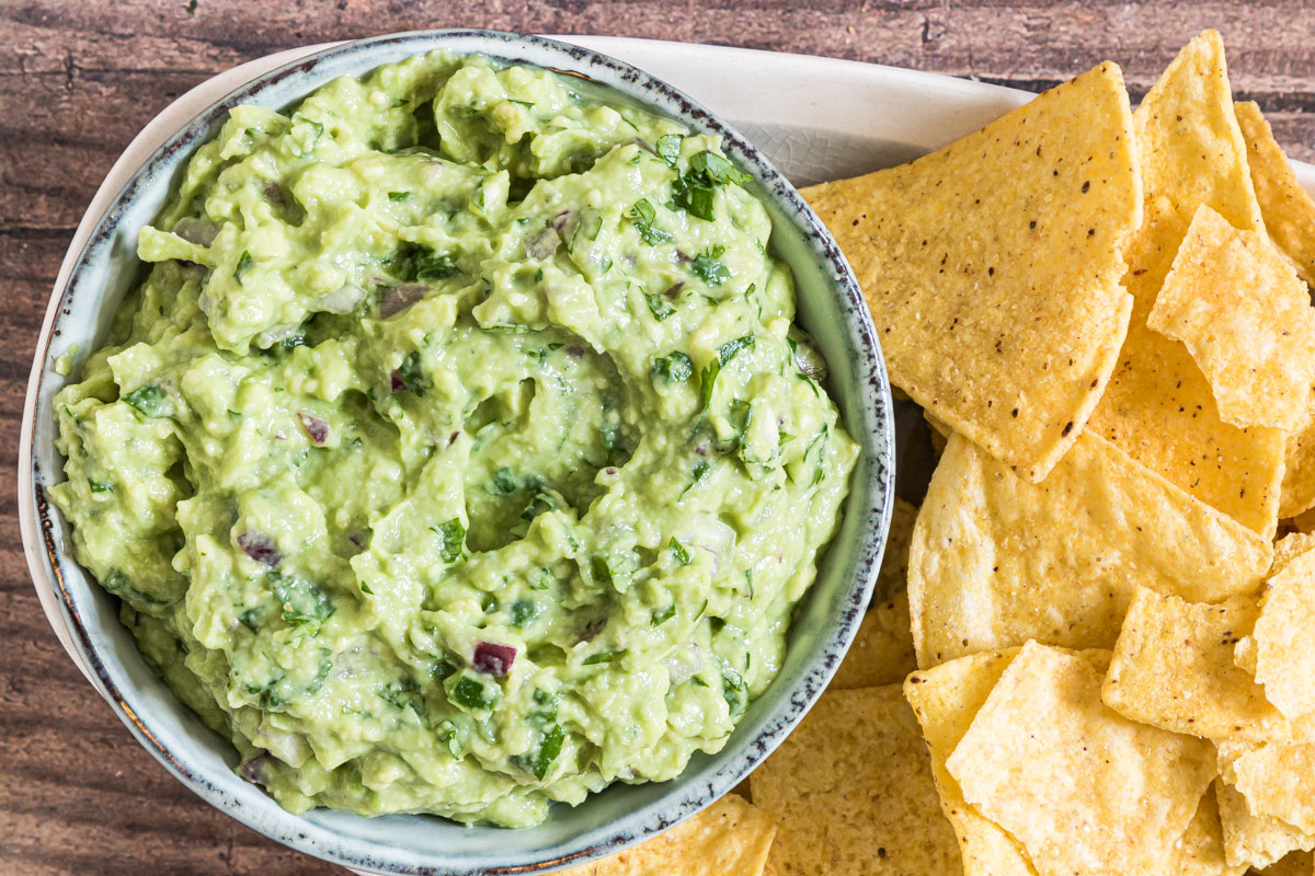a horizontal image of homemade guacamole recipe with adobo on a platter with tortilla chips