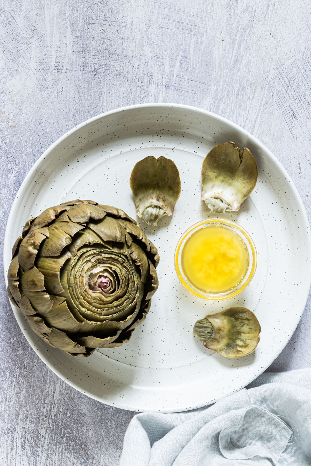 artichoke with an instant pot on a plate of melted butter