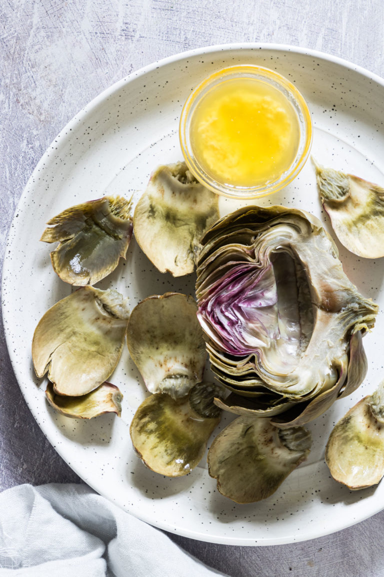 split boiled artichoke with melted butter