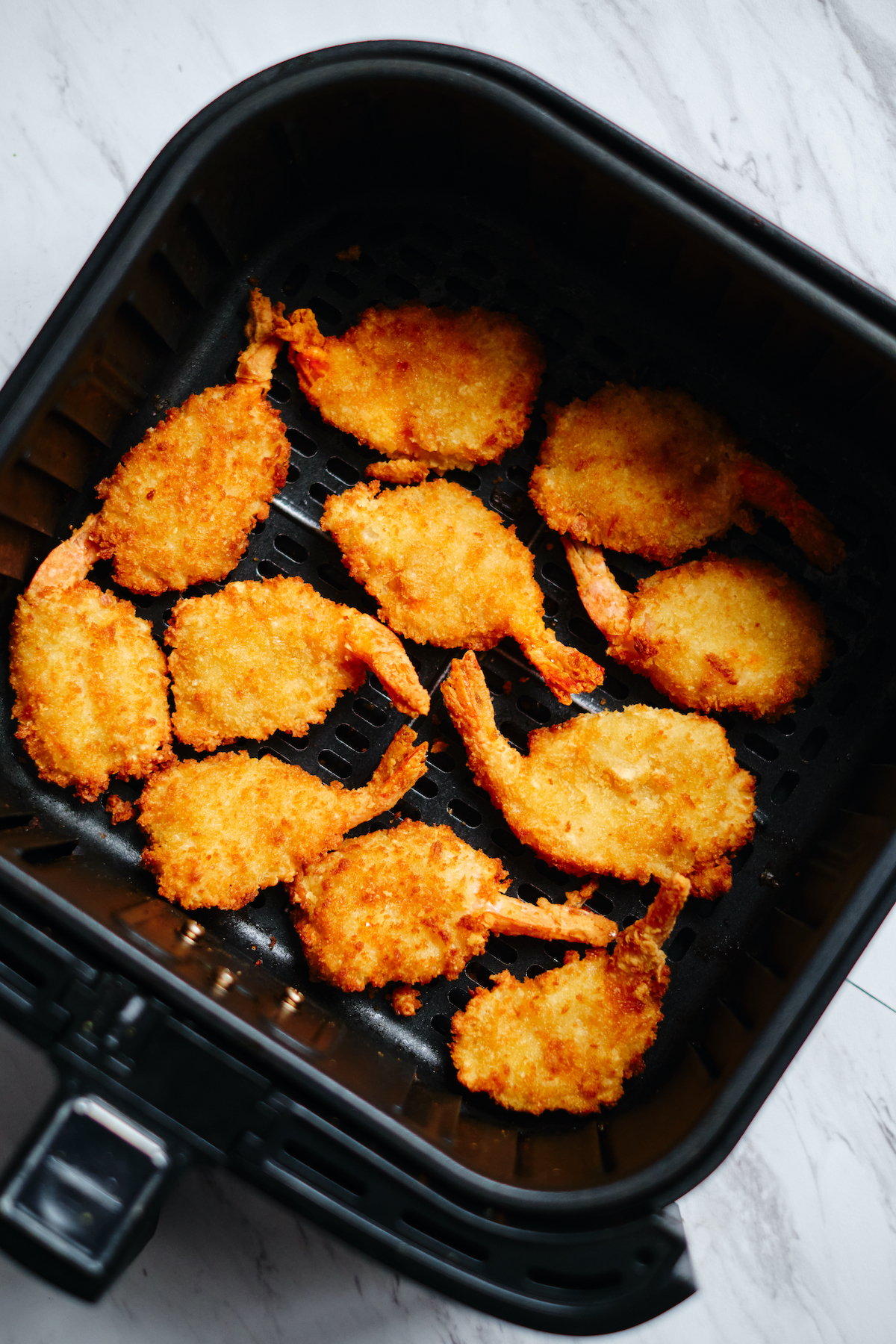 top down view of cooked frozen shrimp in the air fryer basket