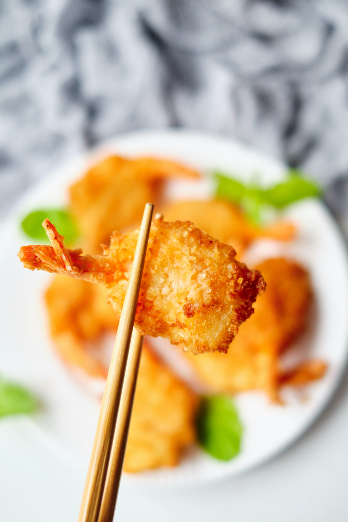 a single shrimp being held with chopsticks