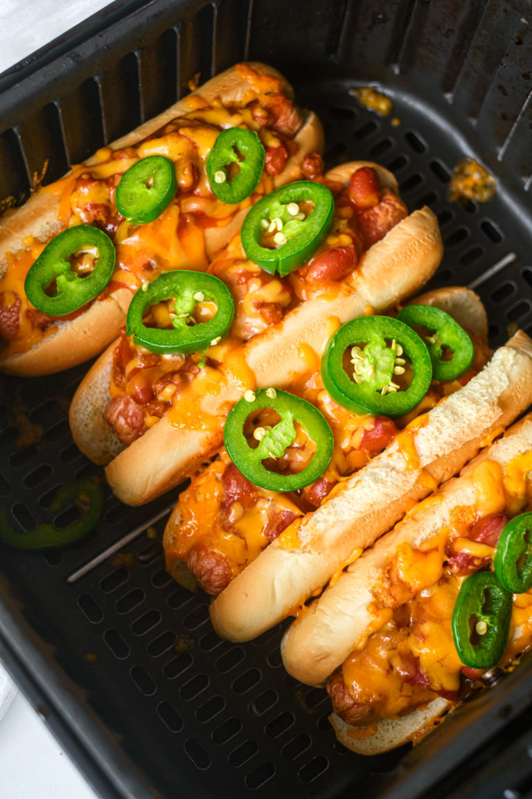 an air fryer basket full of cooked chili cheese dogs with green chilis on top