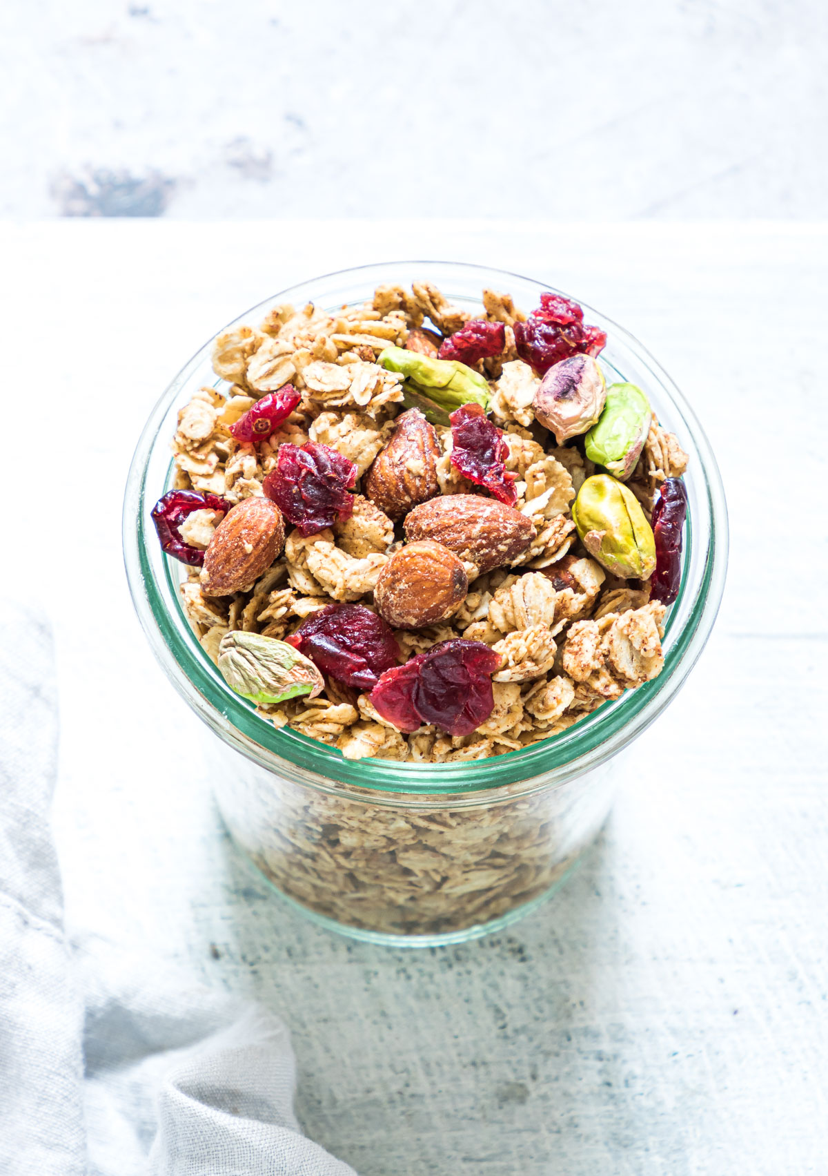 close up of christmas granola in a glass jar with with cranberries, pistachios, and almonds