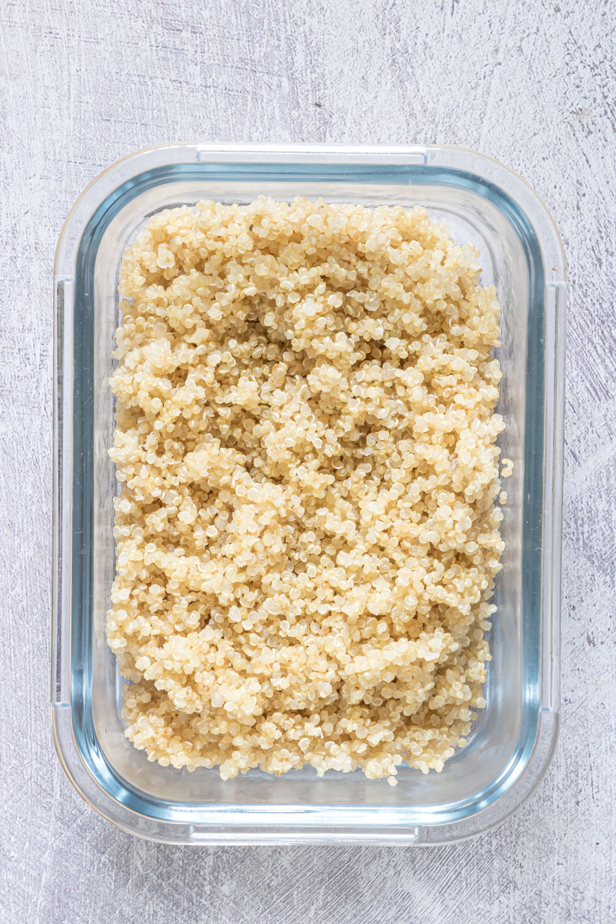 cooked quinoa in a galss meal prep container