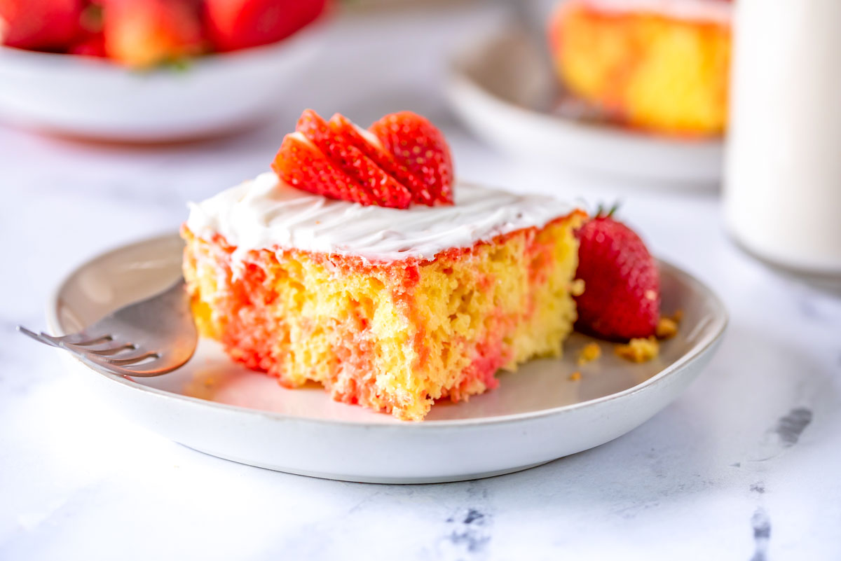 a poke cake with strawberry on a plate with a fork