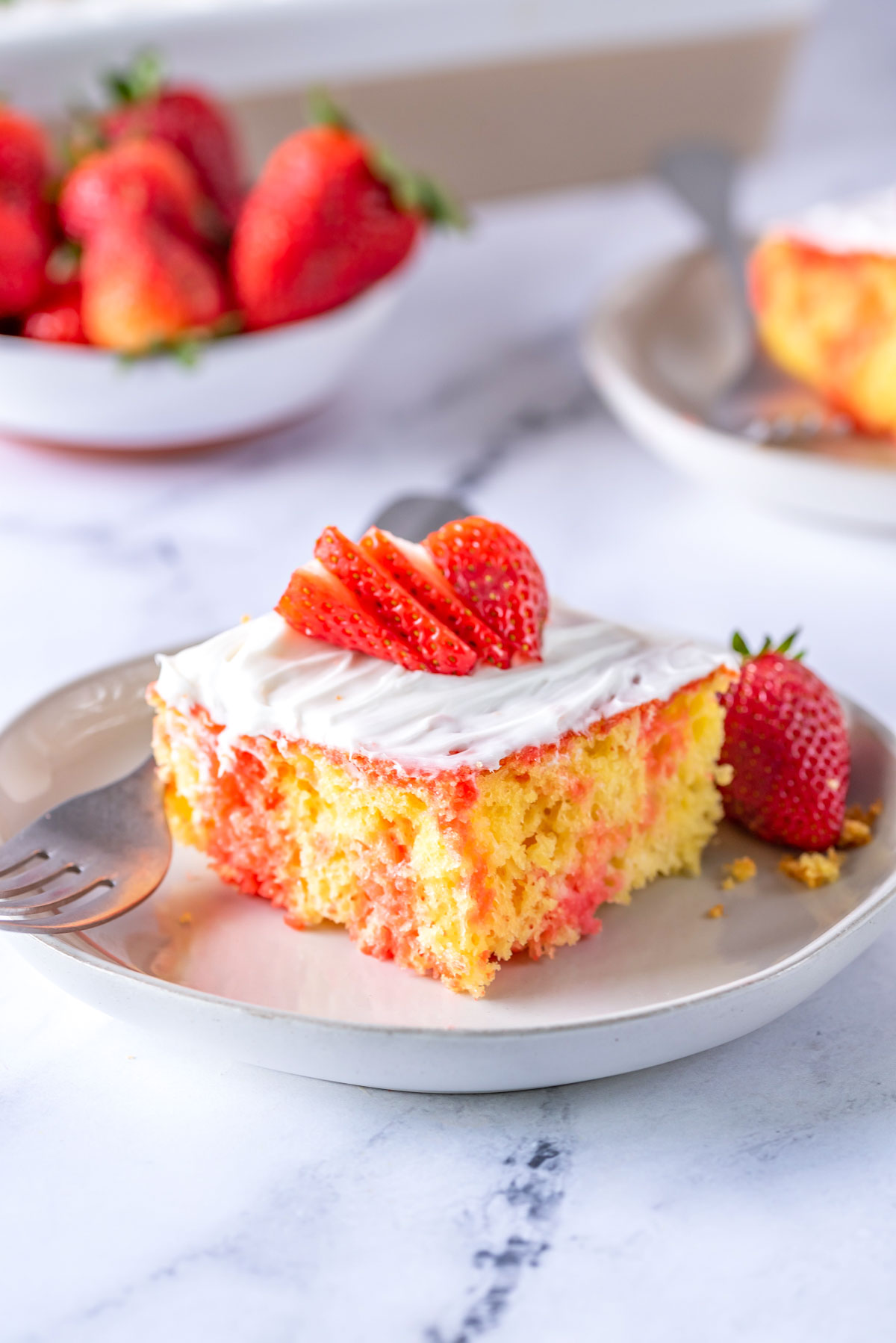 one slice of strawberry poke cake served on a white plate