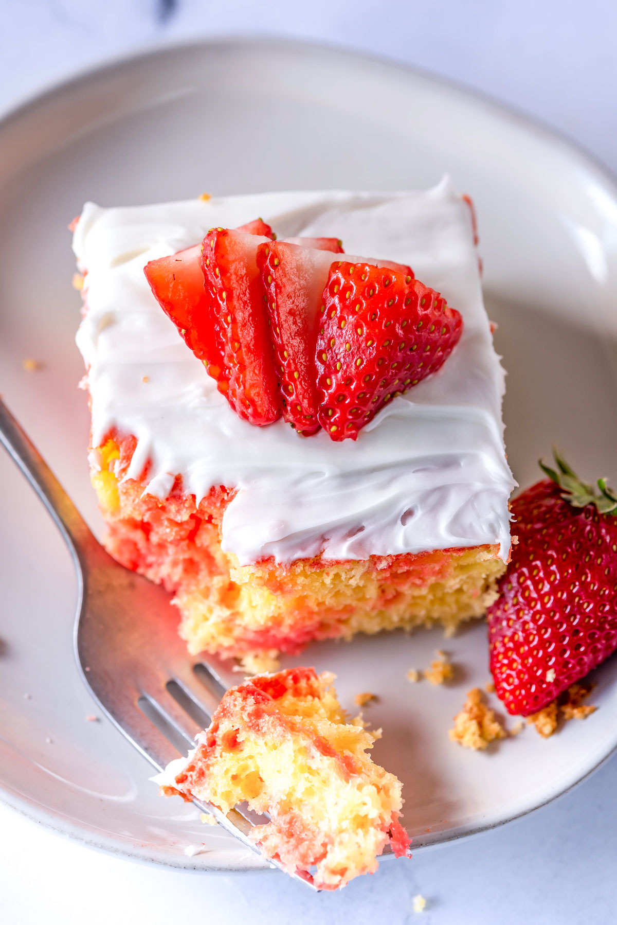a berry poke cake with strawberry slices on the top