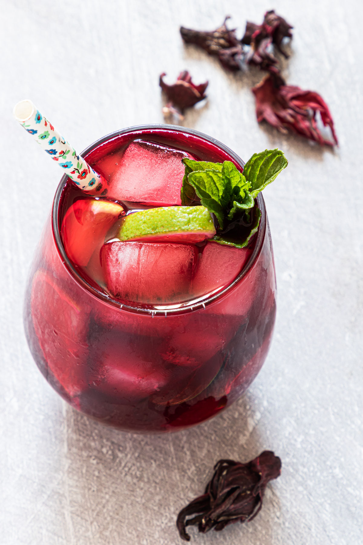 top down view of a glass of hibiscus iced tea with a straw and fresh mint