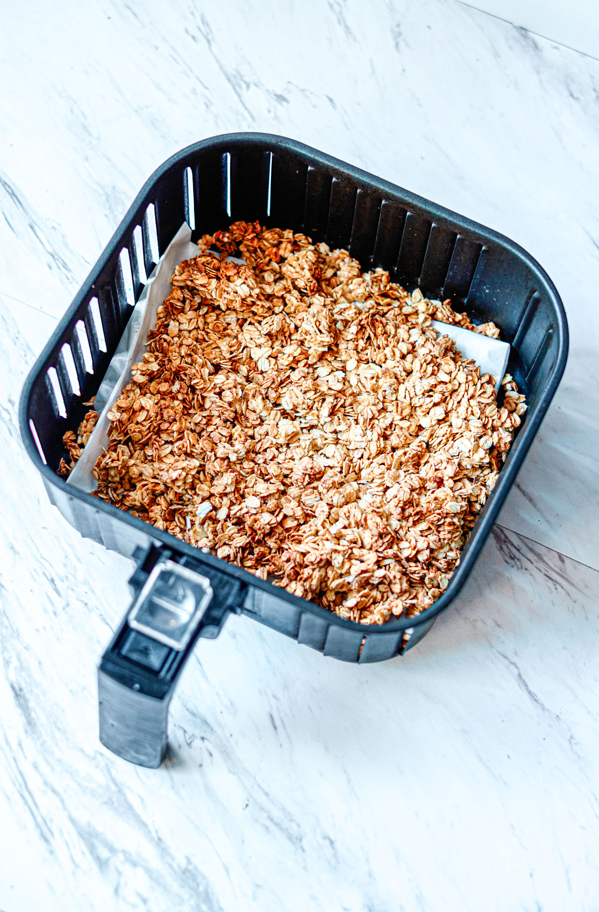 close up of cooked air fryer granola in the air fryer basket