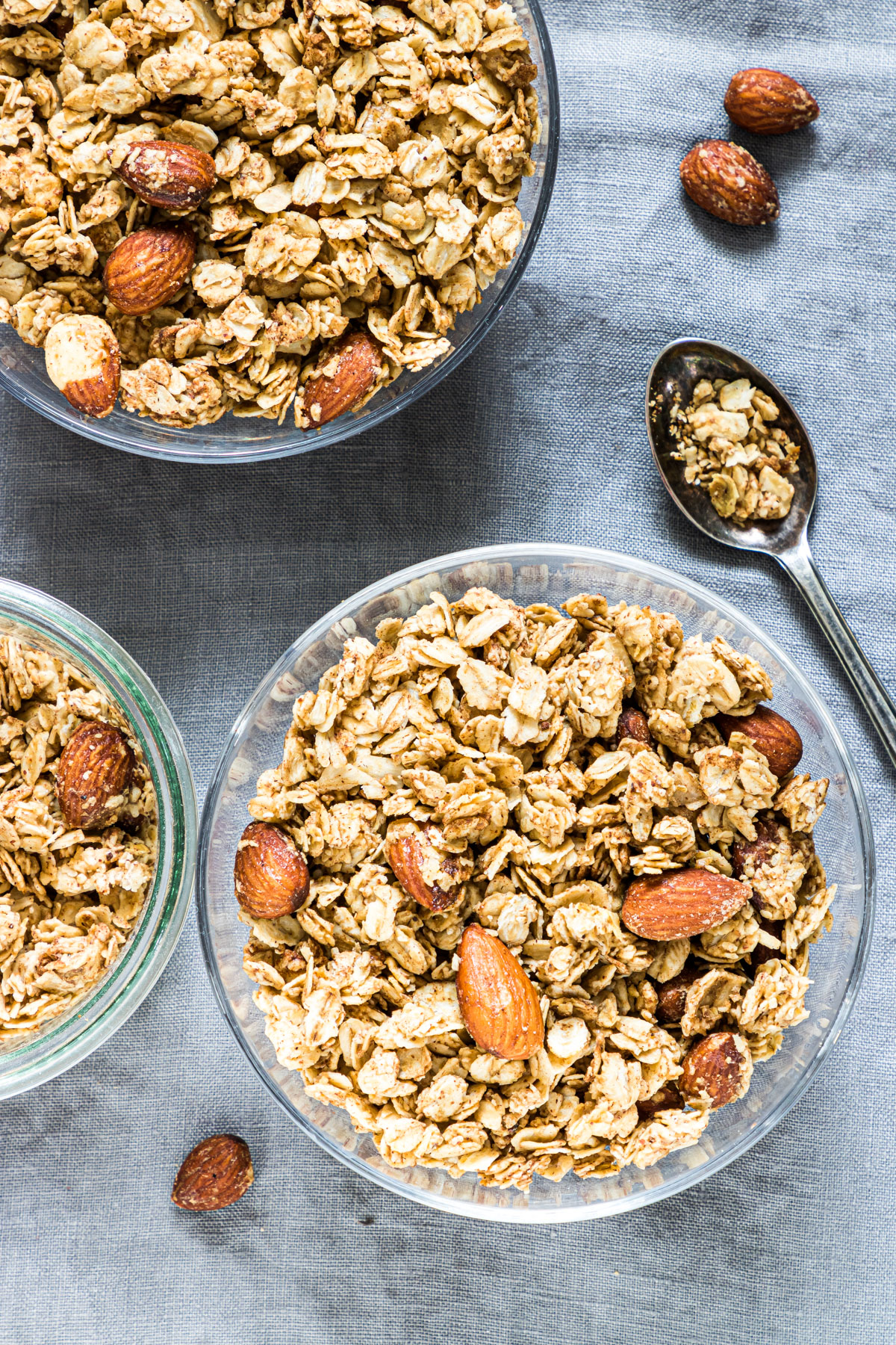 close up of cooked almond butter granola in some bowls with a teaspoon