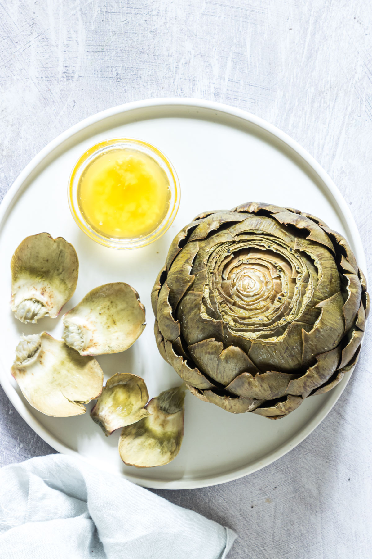 top down view of a completed artichoke served on a white plate
