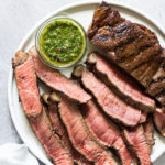 Steak that has been grilled and sliced and served with argentinian chimichurri