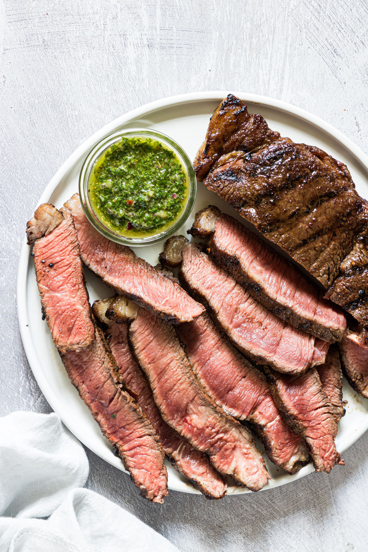sliced grilled steak on a plate with chimichurri sauce