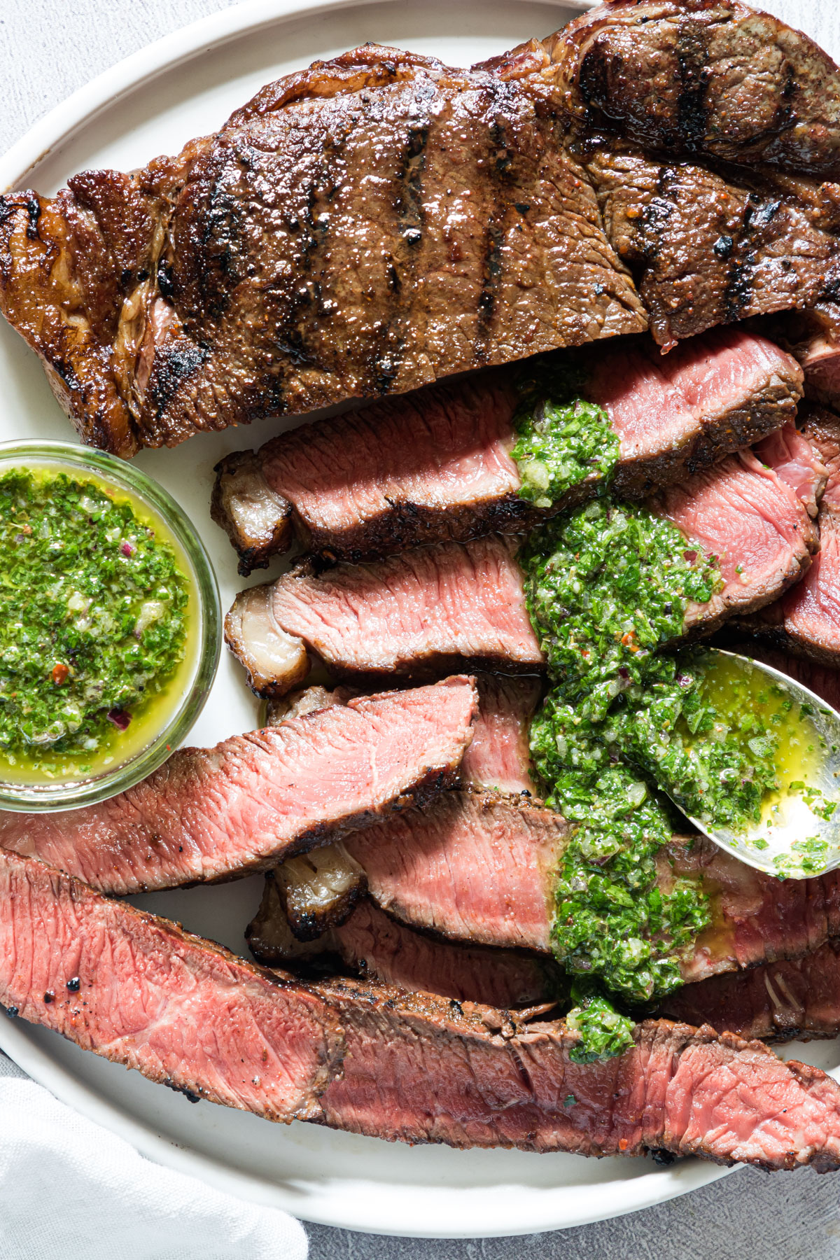 close up of cook steak that has been slices with some chimichurri sauce being added on