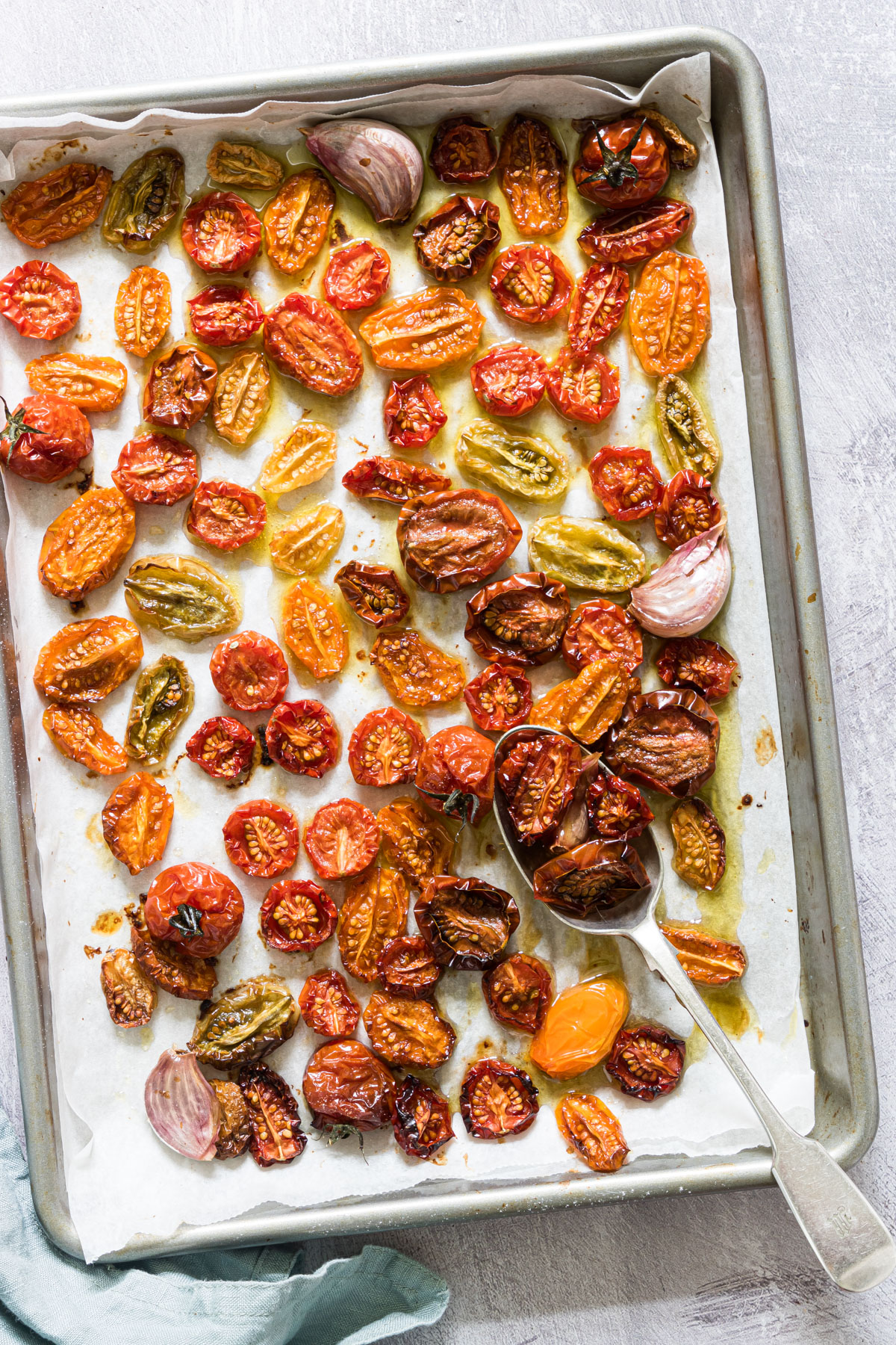 a baking tray of multi colored slow roasted tomatoes and garlic