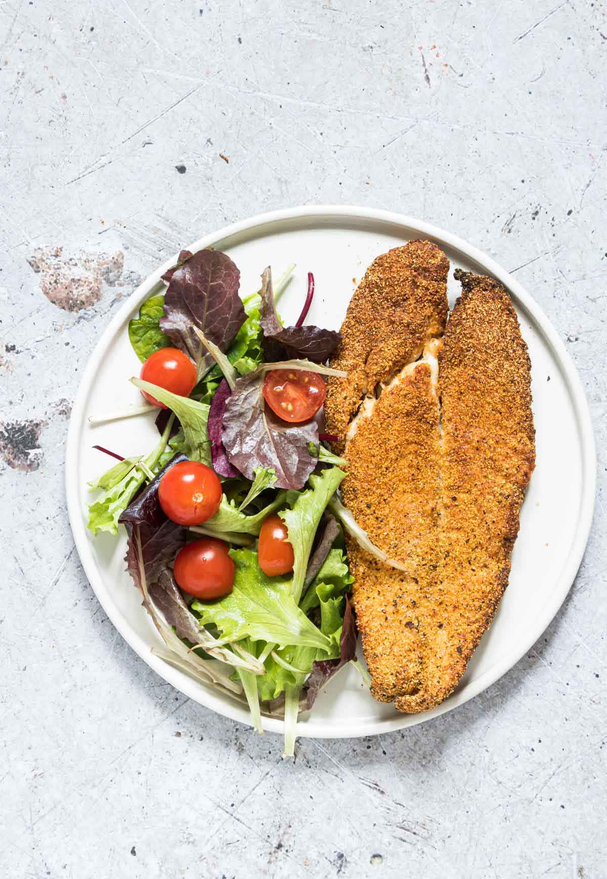 close up of an air fried fish on a plate with some salad
