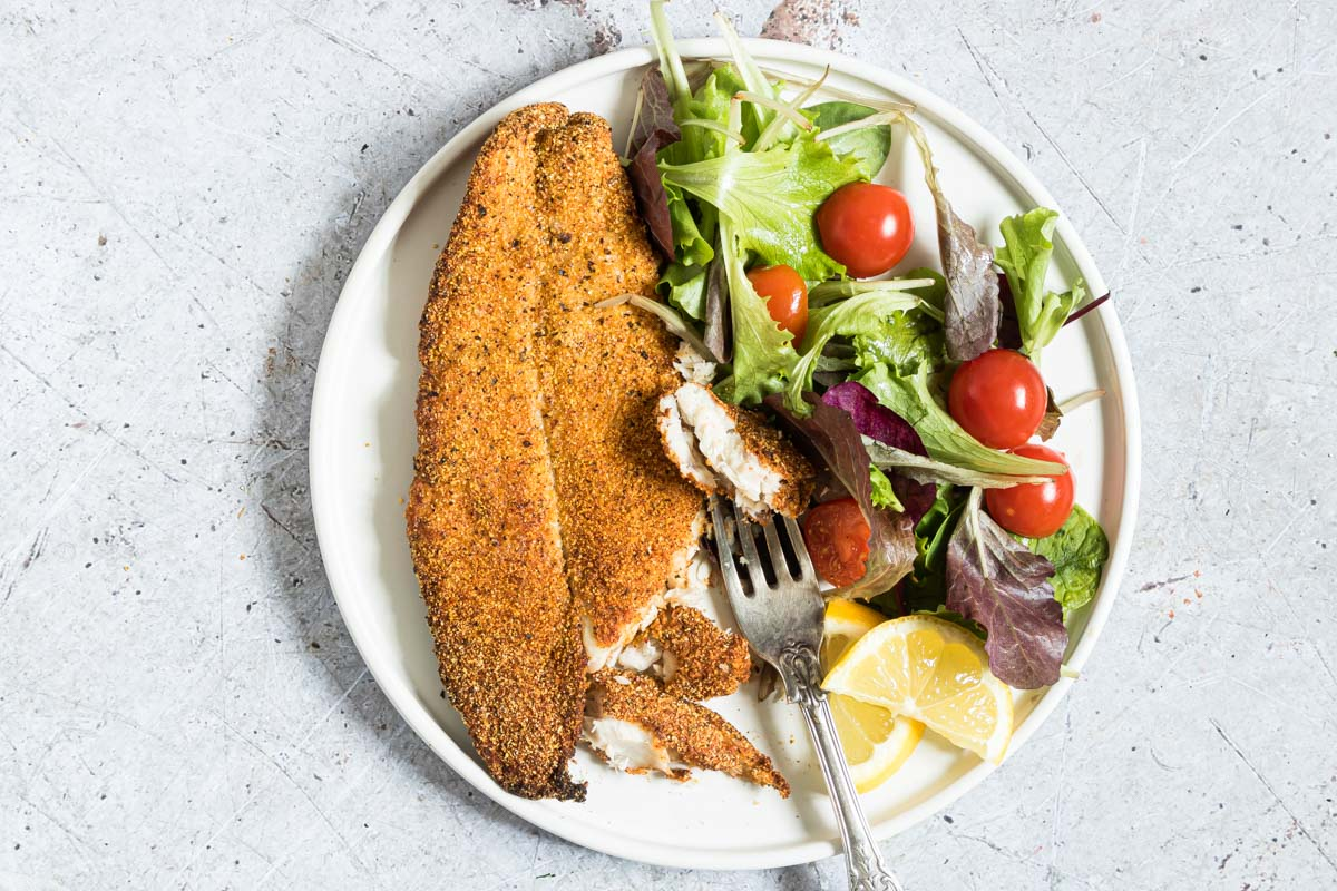 horizontal image of fish fillet on a table with some on a form being eaten