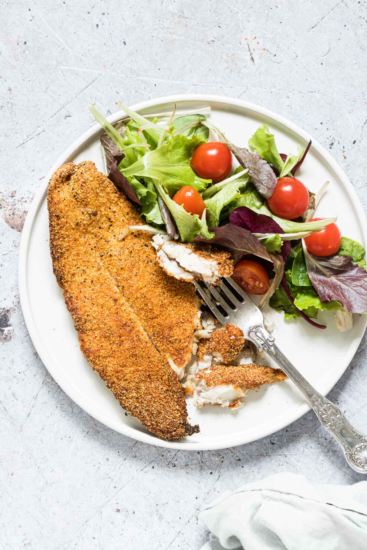 fried fish made in the air fryer on a plate with lettuce, tomatoes and a fork.