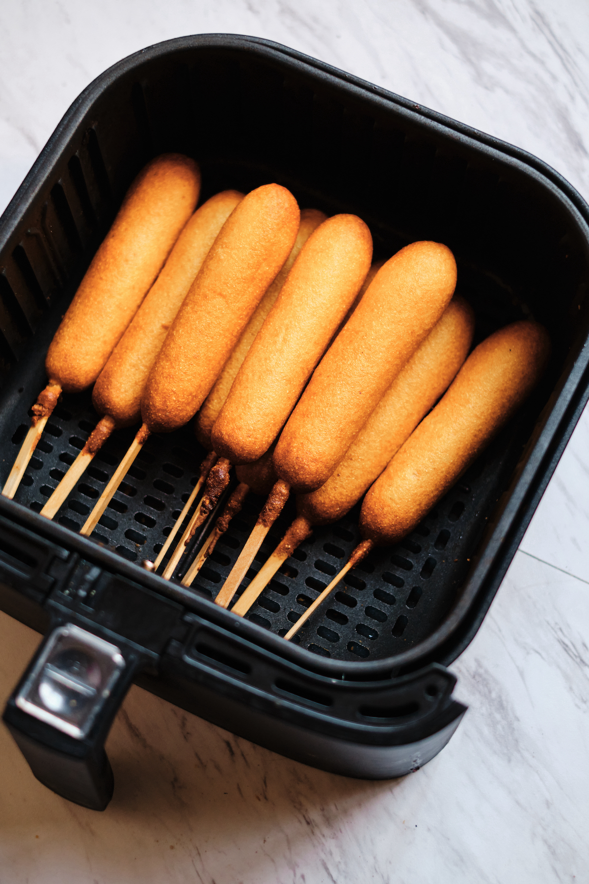 the finished air fryer frozen corn dogs inside the air fryer basket
