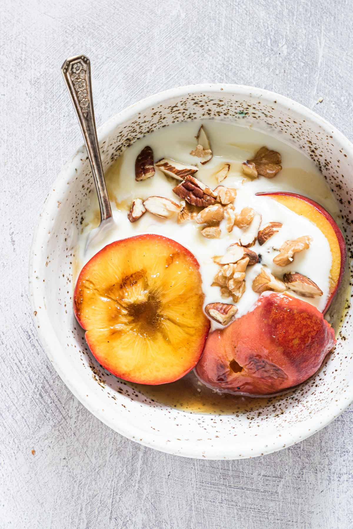 a close up view of one serving of grilled peaches and walnuts with ice cream