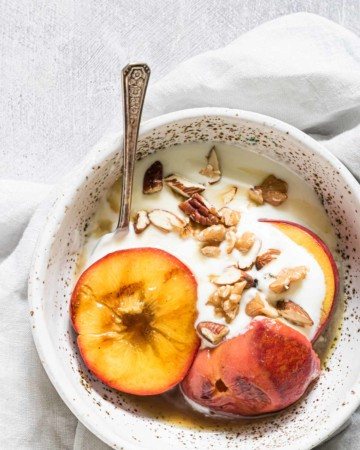 a bowl containing grilled peaches with walnuts and ice cream