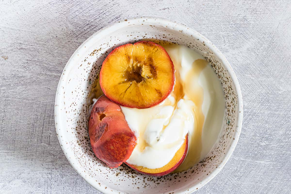 top down view of the completed grilled peaches in a bowl served with ice cream