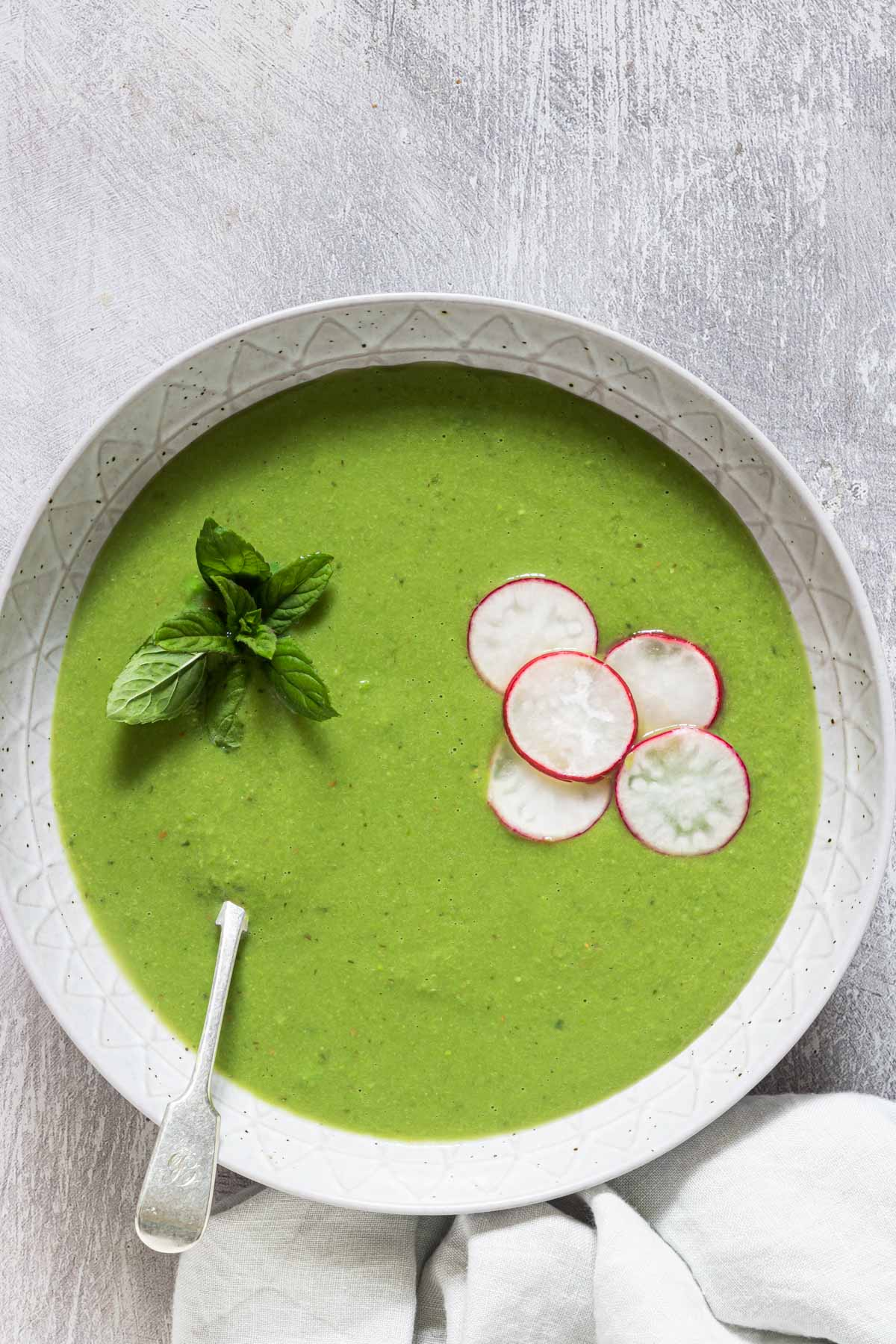 top down view of the finished pea soup served in a bowl and garnished with sliced radishes and mint
