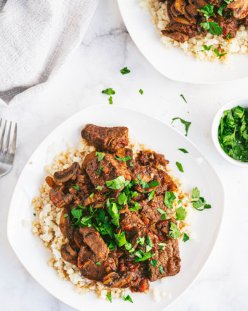 two white plates filled with instant pot swiss steak and rice