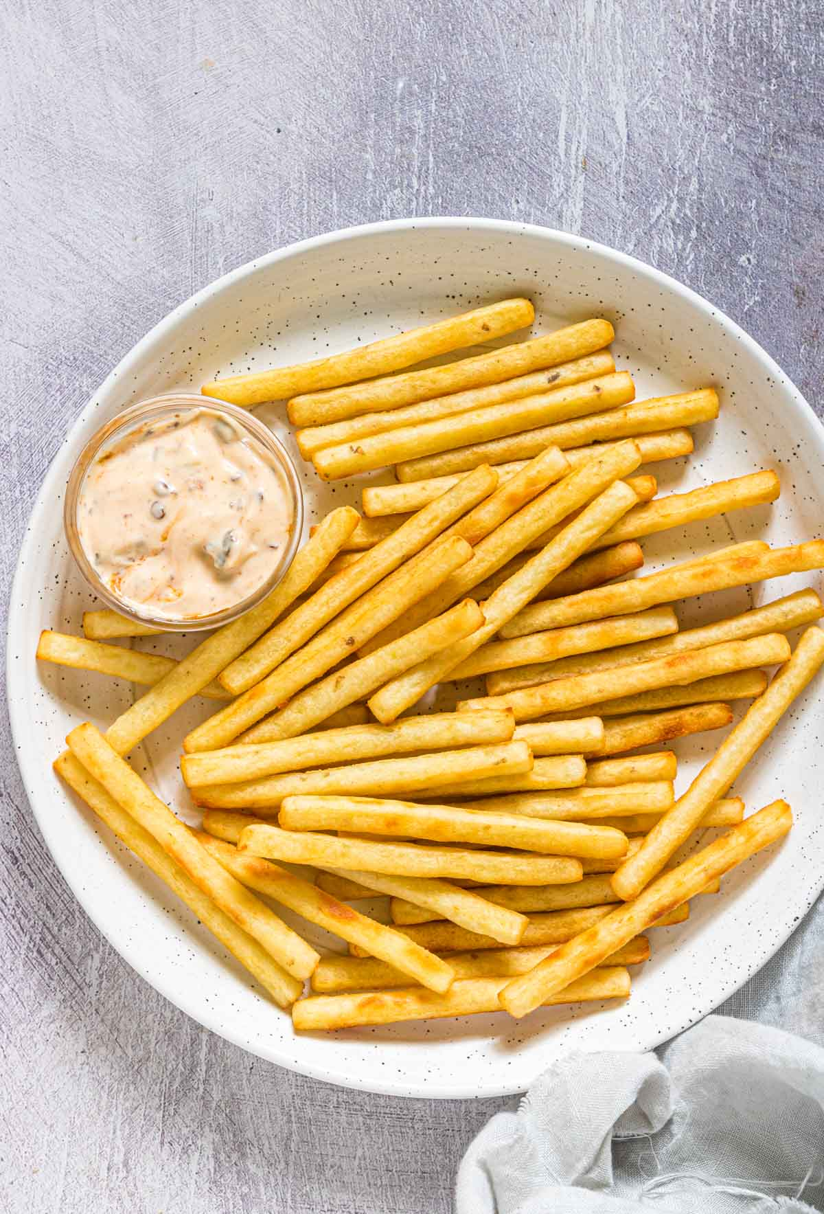 a plate of french fries served with a dish of chipotle aioli dipping sauce