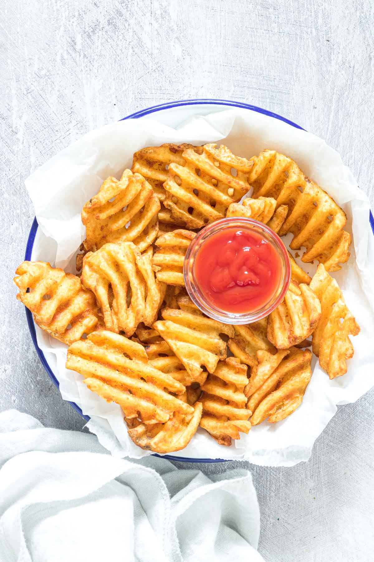 the cooked air fryer frozen waffles fries served in a bowl with a side of ketchup