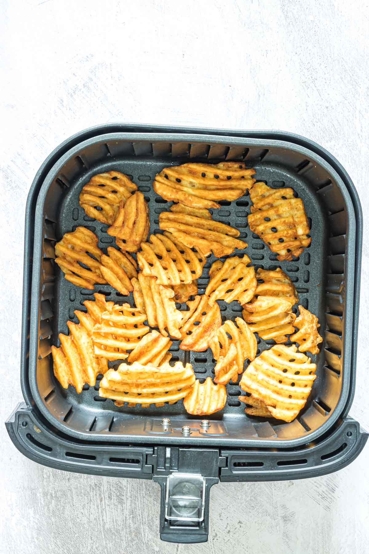 top down view of the cooked frozen waffle fries inside the air fryer basket