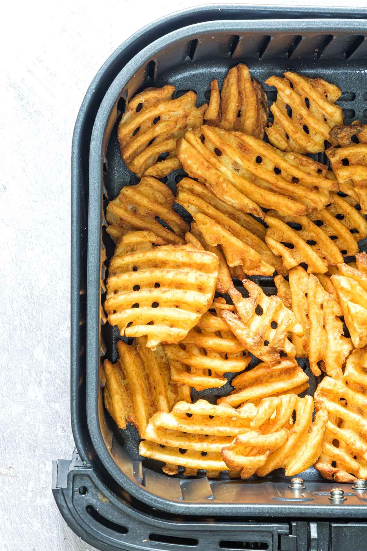 close up view of the frozen waffle fries in air fryer basket