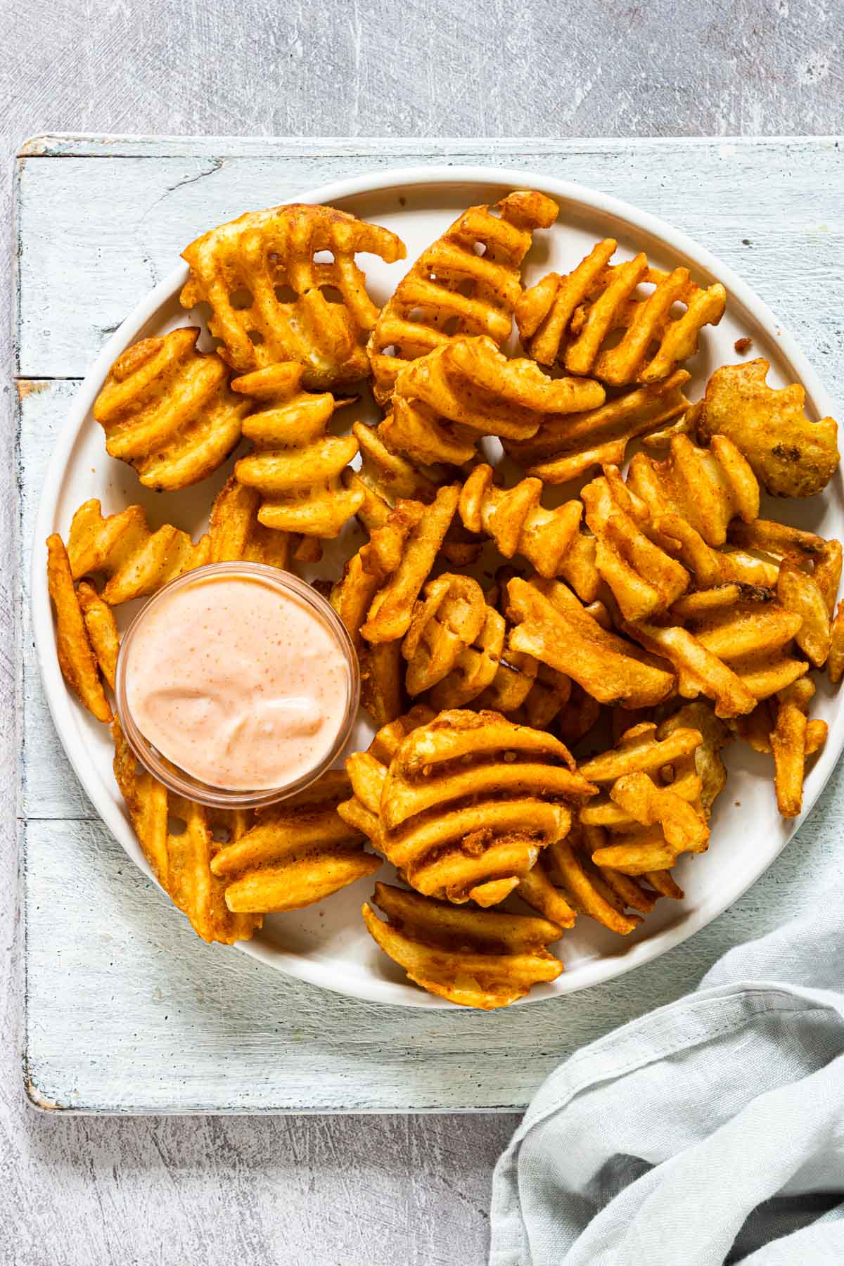 a plate of waffle fries served with the sriracha aioli dipping sauce