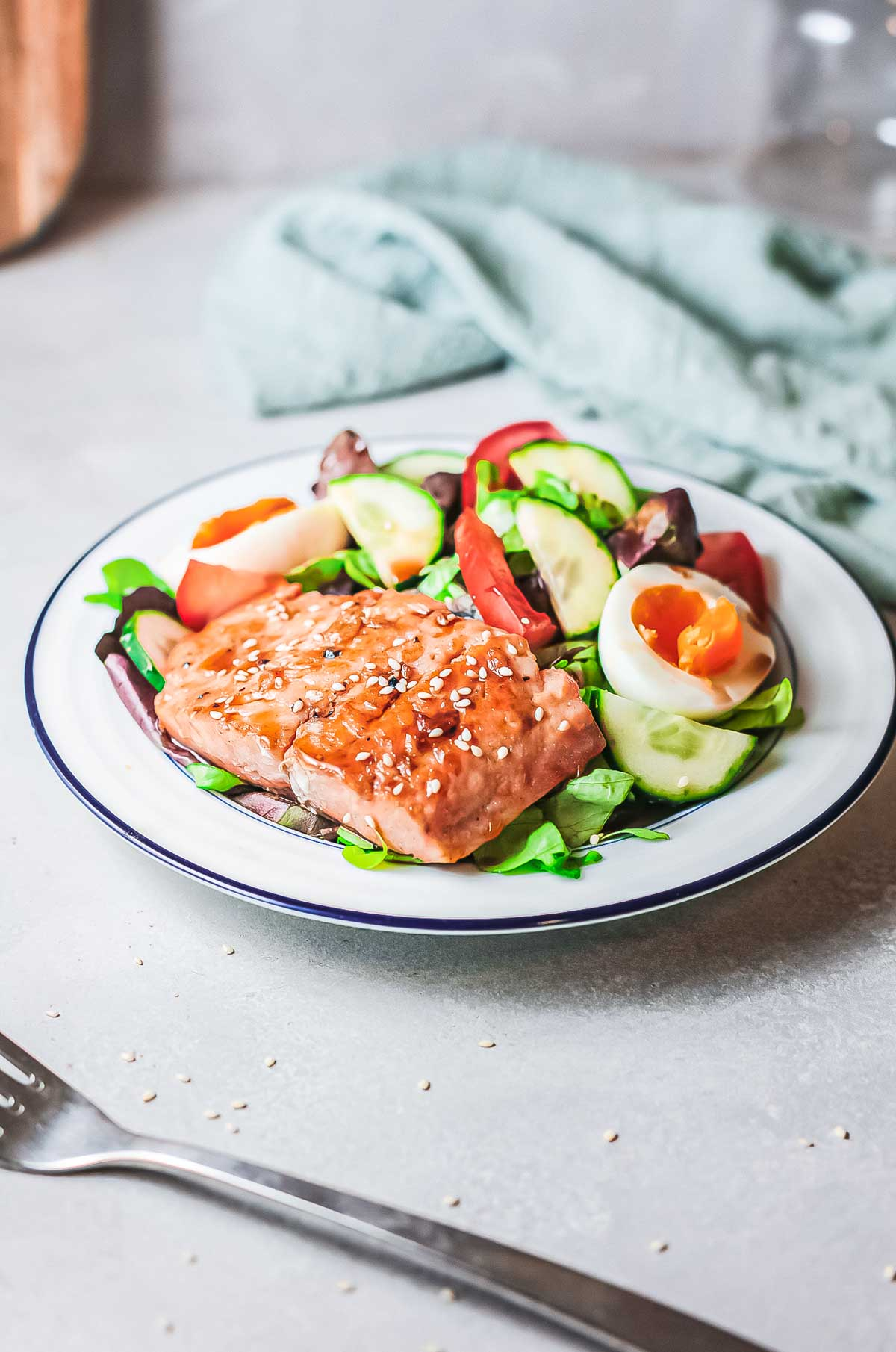 one plate of salmon teriyaki and salad on a table with a fork and blue cloth napkin
