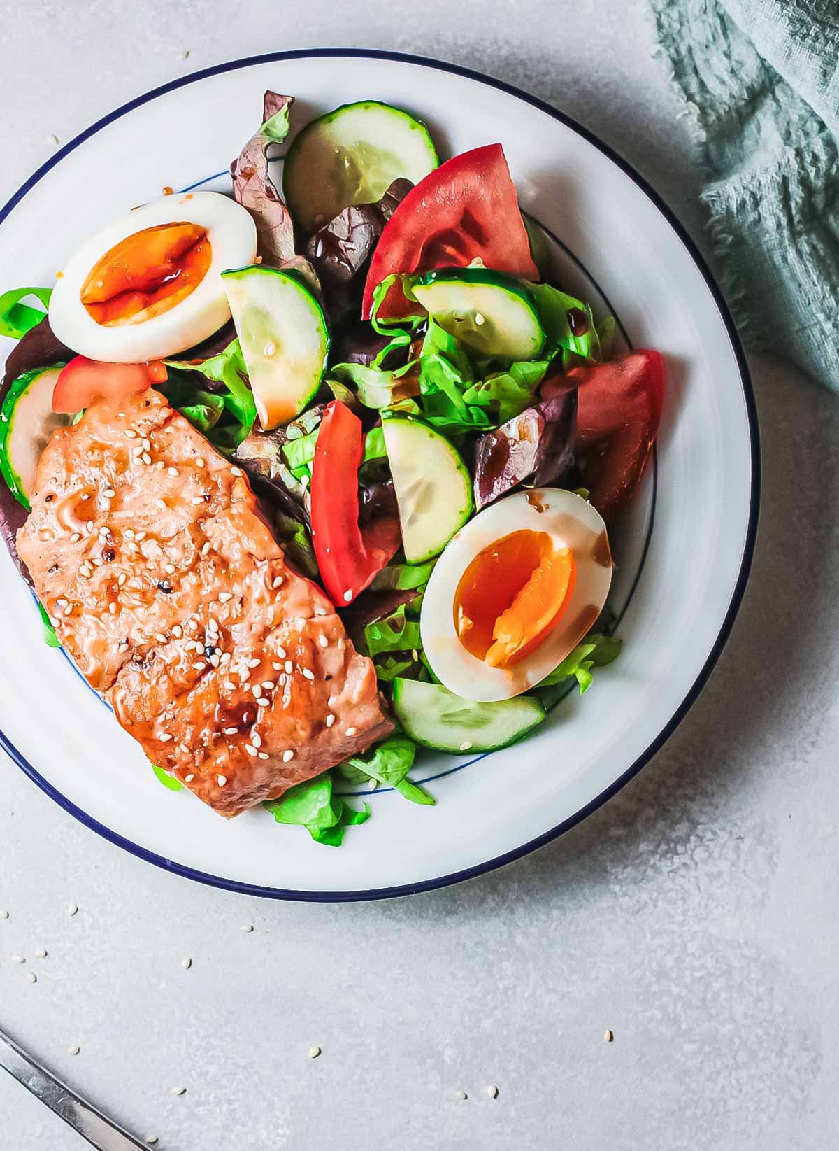 one plate filled with teriyaki salmon and a green salad