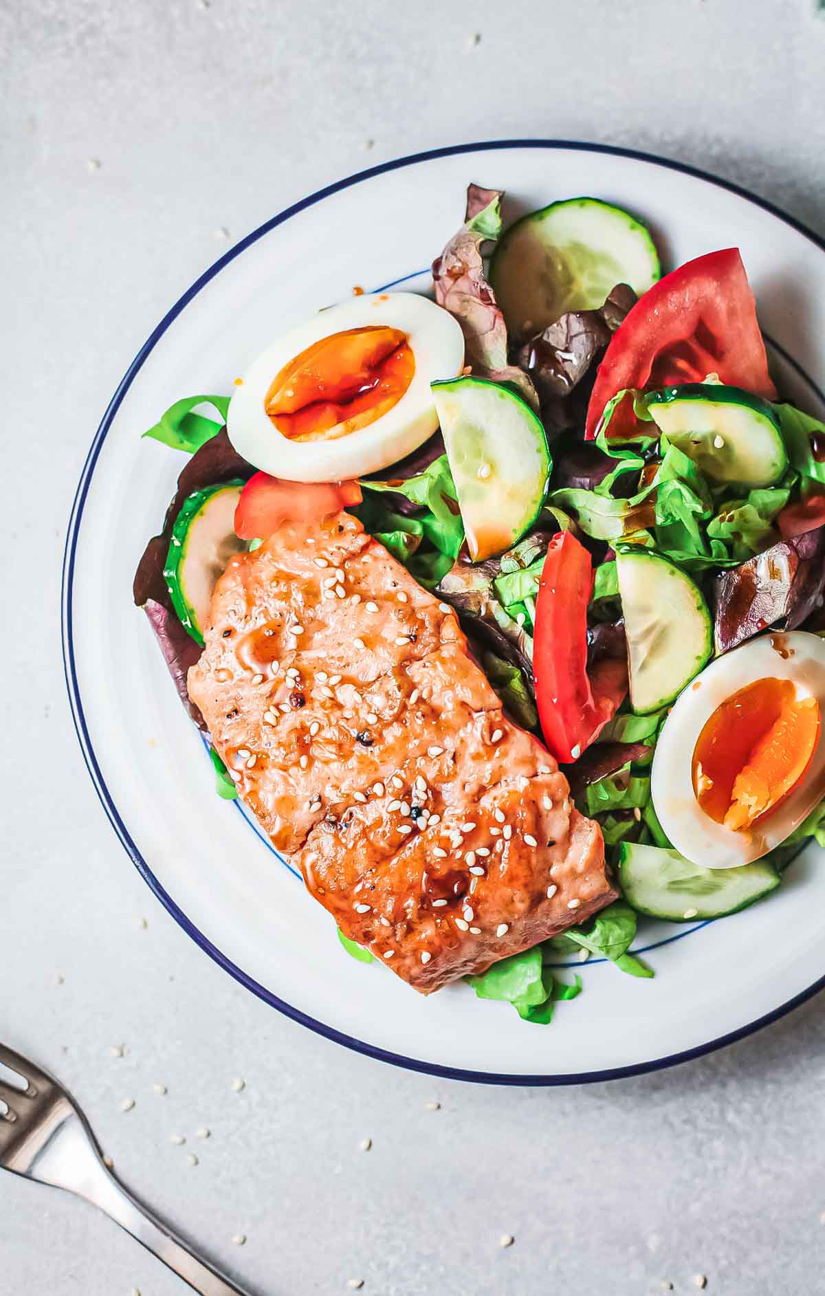 top down view of the completed teriyaki salmon served with a green salad on a white dinner plate